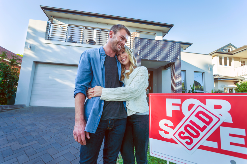 Photograph of young couple after purchasing their first home together.