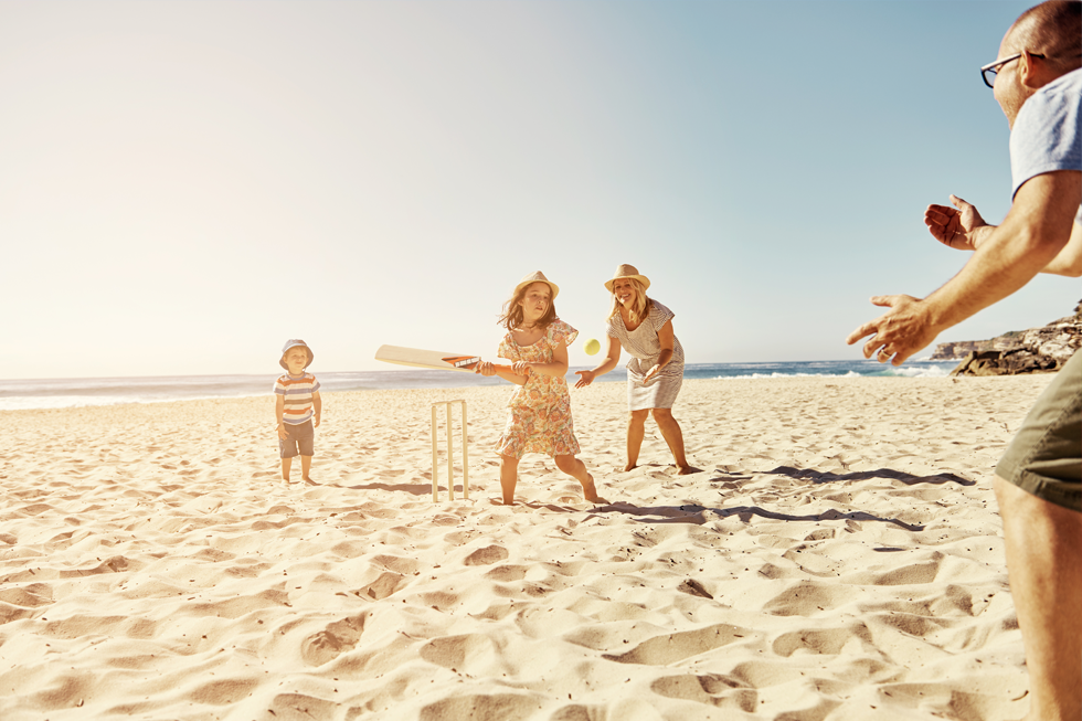A photograph of a happy family playing cricket on the beach.
