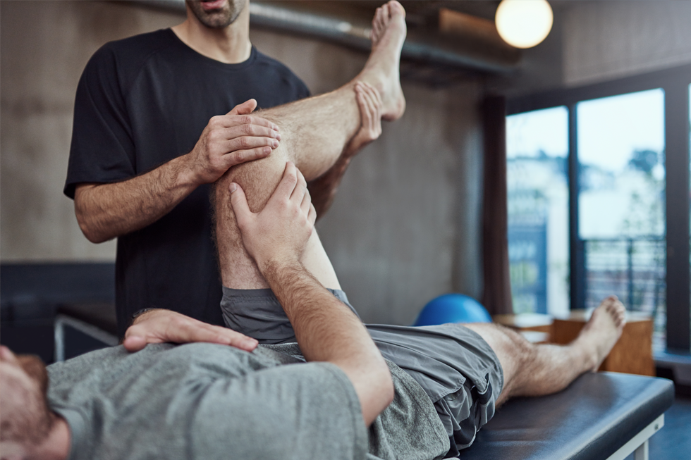 A photograph of a client having therapy on an injured leg.